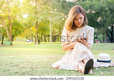 young woman using tablet in park - stock photo