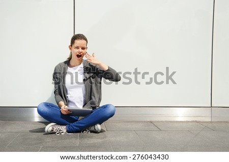 young woman using tablet leaning to wall, very shock emotions - stock photo