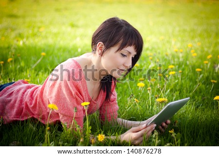 Young woman using tablet outdoor laying on grass - stock photo