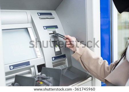 Young woman using the ATM - stock photo