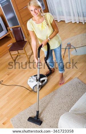 Young woman using vacuum cleaner during regular clean-up indoors - stock photo