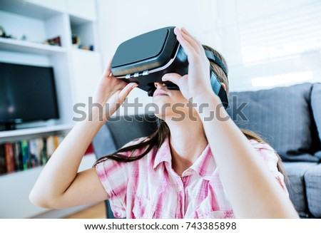 Young woman using virtual reality glasses at home, female wearing VR headset