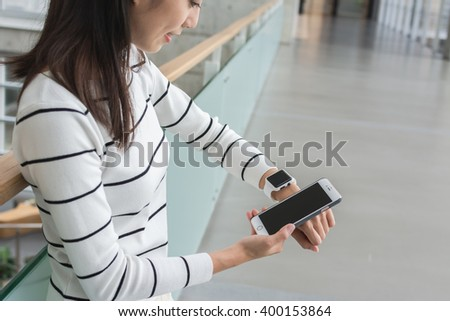 Young Woman using wearable watch connecting to mobile phone - stock photo