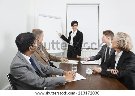 Young woman using whiteboard in business meeting - stock photo