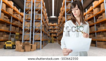 Young woman verifying document with magnifying glass in a distribution warehouse - stock photo