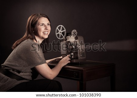 Young Woman Viewing Movies on Old Projector - stock photo