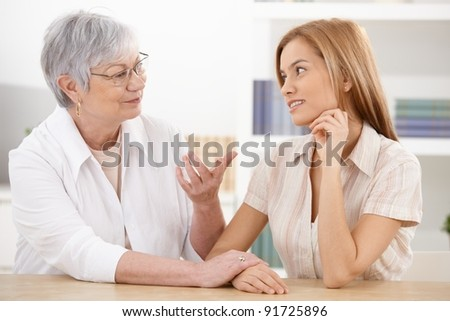 Young woman visiting grandmother at home, chatting, smiling.? - stock photo
