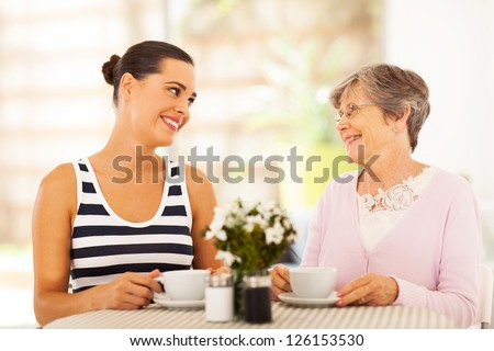 young woman visiting senior mother and having coffee together - stock photo