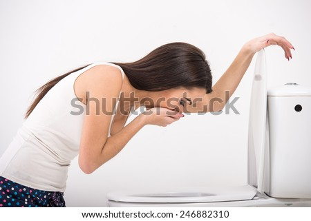 Young woman vomiting into the toilet bowl in the early stages of pregnancy or after a night of partying and drinking. - stock photo