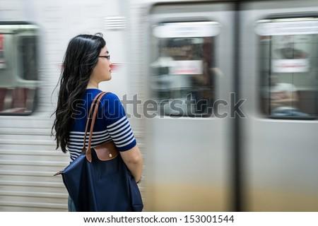 Young woman waiting at subway station - stock photo