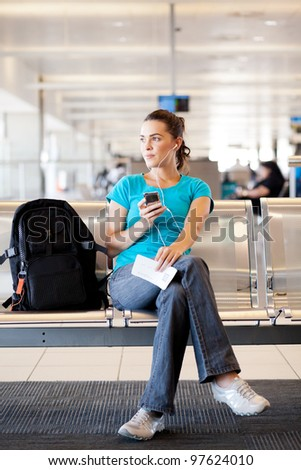 young woman waiting for her flight at airport - stock photo