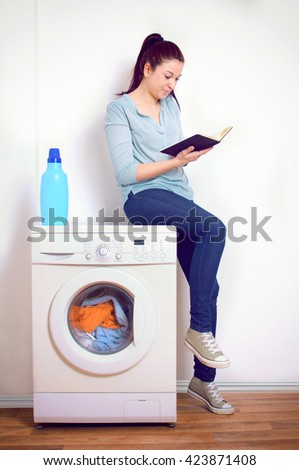 Young woman waiting for the laundry seated by a washing machine - stock photo