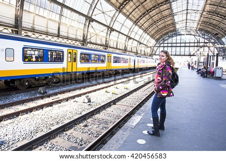 Young woman waiting for the train at central station in Amsterdam the Netherlands