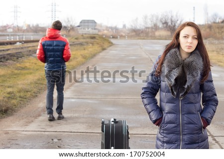 Young woman waiting with her suitcase for a lift in the middle of the road while a young man walks past in the opposite direction - stock photo