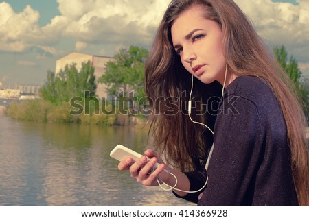 Young woman waiting your call. Dressing in a black wear,  a young caucasian lady is standing by river, holding a mobile phone, with headphones in her ears listening to the music, lost in thought.Toned - stock photo