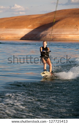 Young woman wakeboarding at Lake Powell in the southwestern US desert.