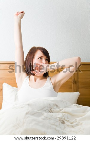 Young woman waking up in her bed