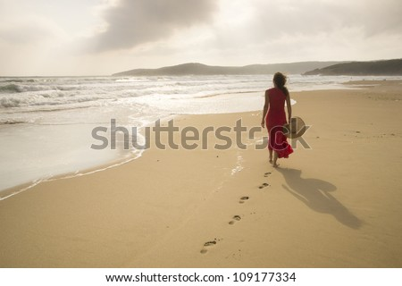 Young woman walk on an empty wild beach towards celestial beams of light falling from the sky