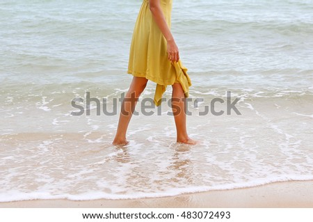 Young woman walking alone on the beach