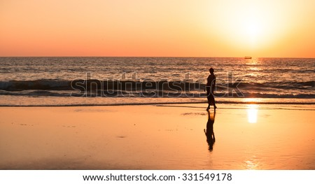 Young woman walking along empty coast, leaving footprints in the sand. Goa.Young woman silhouette walking along the beach of the sea during an amazing sunset - stock photo