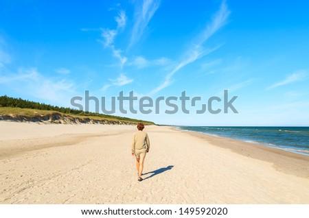 Young woman walking along sandy beach, Slowinski National Park near Leba, Poland  - stock photo