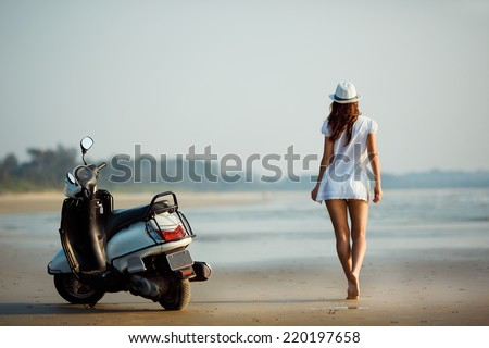 Young woman walking along the beach. Sexy girl on the beach, standing next to Motorcycles. Girl stretches into the distance. - stock photo