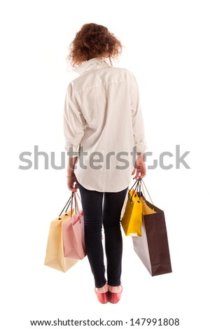 Young woman walking away with shopping bags, isolated on white background - stock photo