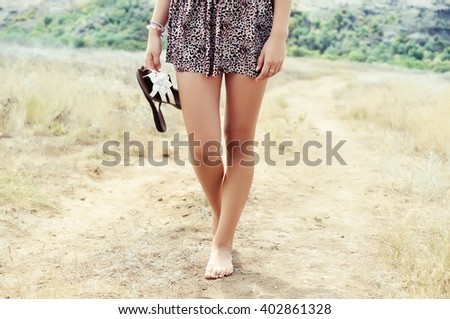 Young woman walking barefoot on a road - stock photo