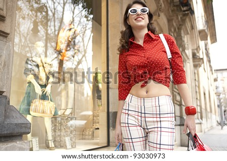 Young woman walking by a shop window, holding shopping bags. - stock photo