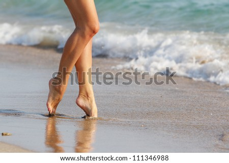 young woman walking by beach - stock photo