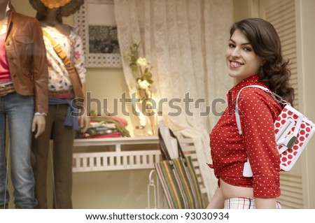 Young woman walking by shop window. - stock photo