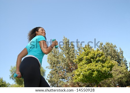 Young woman walking energetically through the park - stock photo
