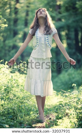 Young woman walking in a forest. Delighting good weather.