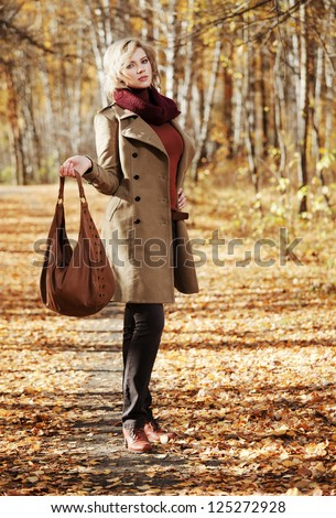 Young woman walking in autumn forest - stock photo