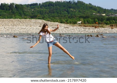 Young woman walking in cold mountain river with white horse on background - stock photo