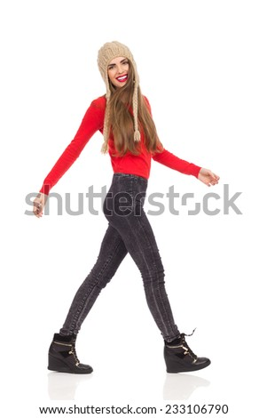 Young woman walking in red top, black jeans and winter cap. Side view. Full length studio shot isolated on white. - stock photo