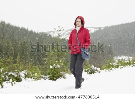Young woman walking in snowy highland landscape
