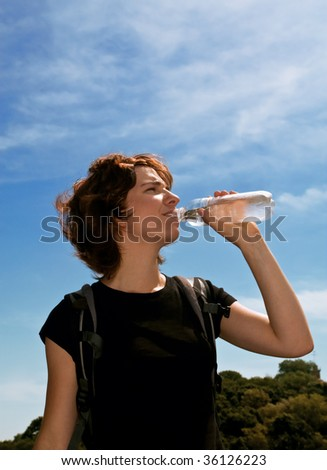Young woman walking in the city and refreshing herself with cold fresh water