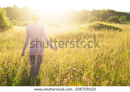 Young woman walking in the field toward the sun holding a poppy flower. - stock photo