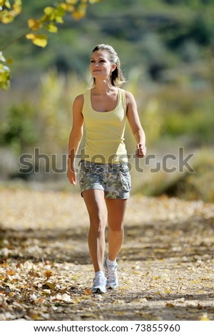 young woman walking in the park in summer - stock photo