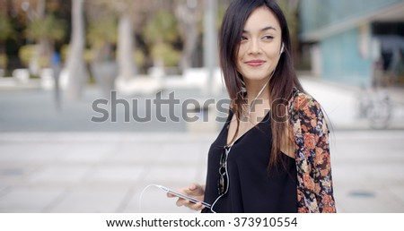 Young woman walking listening to music - stock photo