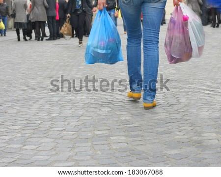 Young woman walking on a busy city street and holding colored plastic shopping bags with various groceries, high cost of living in the city - stock photo