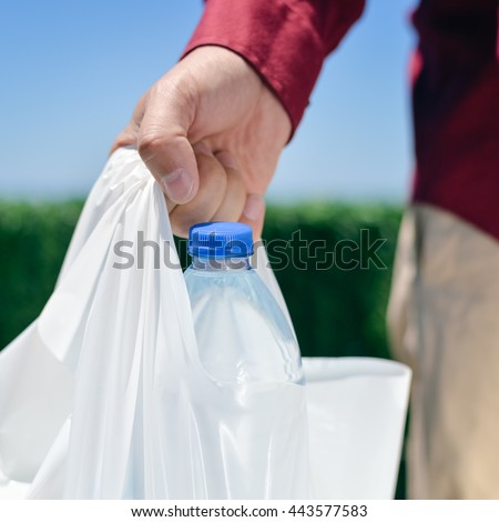 Young woman walking on a busy city street and holding colored plastic shopping bags with various groceries, high cost of living in the city
