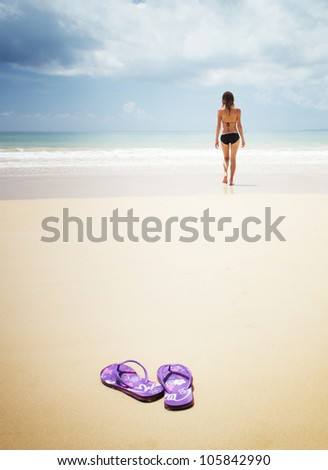 Young woman walking on a perfect sandy beach and going to swim in a sea - stock photo