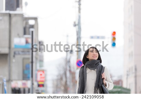 Young woman walking on a winter city. - stock photo