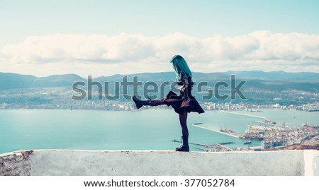Young woman walking on high edge over the sea bay
