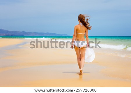 Young woman walking on ocean beach