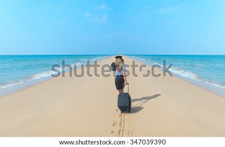 Young woman walking   on the beach with suitcase and hat .