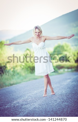 young woman walking on the road barefoot