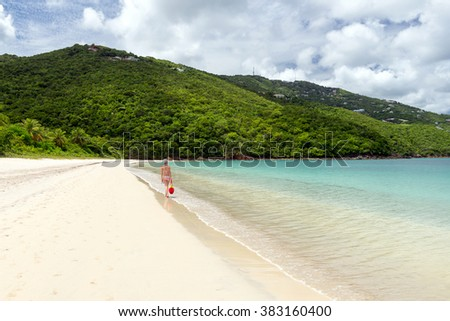 young woman walking on the shore of a tropical beach in the Caribbean - stock photo